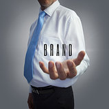 Businessman holding the word brand