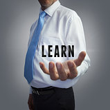 Businessman holding the word learn