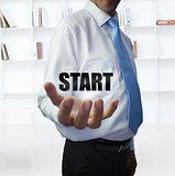 Elegant businessman holding the word start