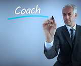 Businessman writing the word coach