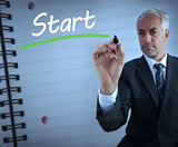 Businessman standing and writing the word start