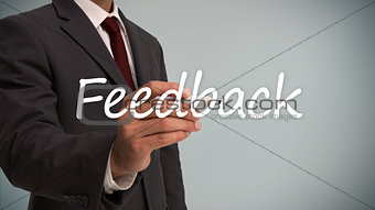 Businessman writing the word feedback