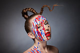 Girl with braid and artistic makeup over dark background