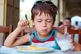 Cute little boy having delicious breakfast