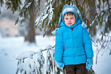 Cute little boy playing outdoors in a winter forest