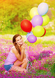 Pretty girl holding colorful balloons