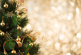 Gold Christmas background of defocused lights with decorated tre