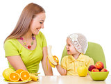mother feeding little girl with healthy food sitting at table is
