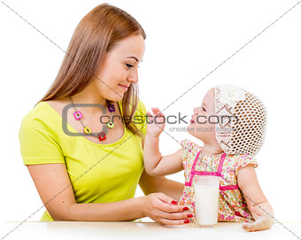 mother giving milk glass to little girl sitting at table isolate