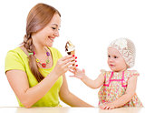 mother giving ice cream to little girl sitting at table isolated