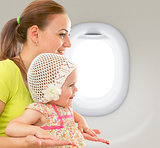 Happy mother and child sitting together in jet cabin near window
