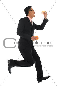 Asian businessman in hurry eating bun