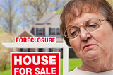 Depressed Senior Woman in Front of Foreclosure Real Estate Sign