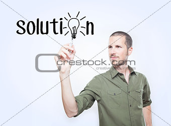 "Young man writing the word ""solution"""