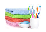 Four colorful toothbrushes, soap and towels