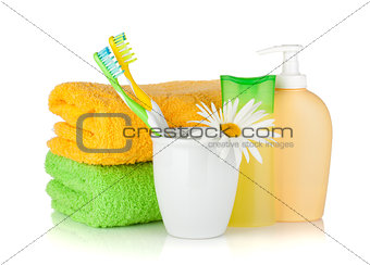 Toothbrushes, shampoo bottles, two towels and flower