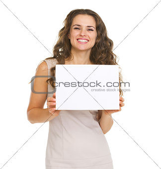 Portrait of happy young woman showing blank paper