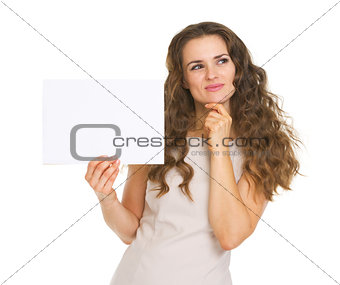 Thoughtful young woman holding blank paper