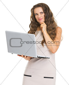 Thoughtful young woman with laptop