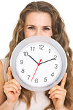 Young woman hiding behind clock