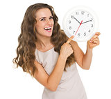 Smiling young woman pointing on clock