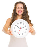 Closeup on clock in hand of smiling young woman