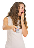 Yawing young woman switching channels with tv remote control