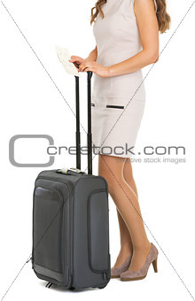 Closeup on young tourist woman with wheel bag and air tickets