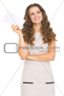 Thoughtful young woman holding letter
