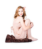 Isolated pinup girl sitting on soft blanket