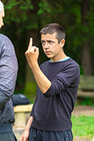 Boy showing middle finger to adult