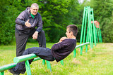 Father and son engaged in athletic exercises