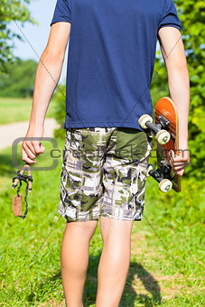 Boy with a slingshot and skateboard on rural road