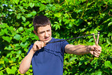 Boy with a slingshot near the bush