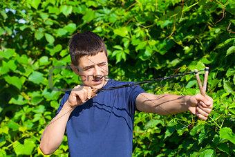 Boy with a slingshot near the bush