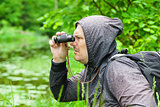 Man with binoculars watching birds at the lake