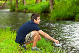 Boy with paper boat near the river