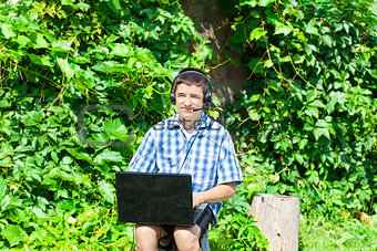 Boy with headphones, Mic and PC at outdoors