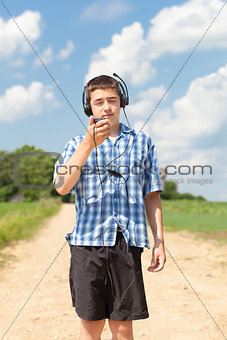 Boy with headphones and Mic on rural road in summer