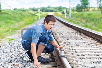 Boy puts stones on railway tracks