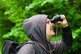 Man with binoculars watching birds in the park