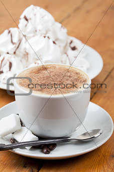 Cappuccino with foam and meringues on white plate