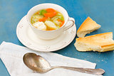 Fish soup with silver spoon