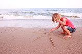 girl draws a sun in the sand on the beach