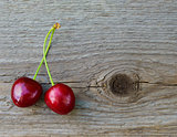 Two Fresh Ripe Red Sweet Cherries on Wooden Background