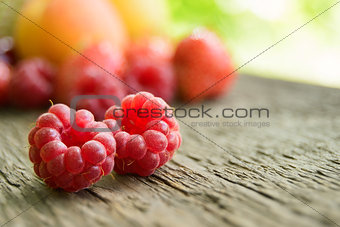 Ripe Sweet Raspberries and Fruits on the Wooden Table