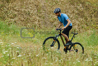 Mountain Biker Riding His Bike Through the Meadow