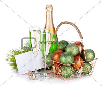 Champagne bottle, glasses, empty gift card and christmas balls
