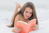 Happy young girl reading a book