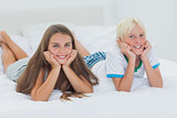 Cheerful siblings lying on bed